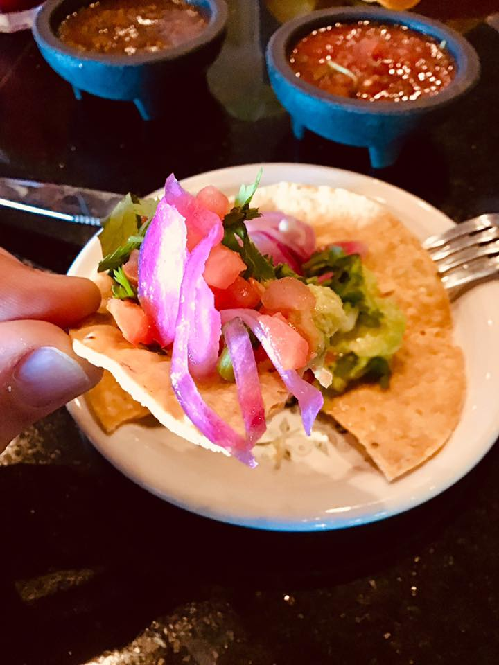 guacamole and pickled red onions on tostada
